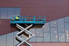 Constructeur sur une plate-forme d'ascenseur de ciseaux à un chantier de construction Image libre de droits