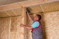 Constructeur Using Cordless Drill sur le cadre de Chambre photos libres de droits