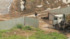 Constructeurs allant le long d'une barrière de chantier de construction banque de vidéos