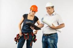 Constructeurs dans le masque ou le casque discutant des modèles avec le comprimé images libres de droits