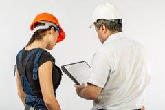 Constructeurs dans le masque ou le casque discutant des modèles avec le comprimé image stock