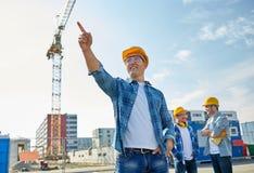 Constructeurs dirigeant le doigt de côté sur la construction Images libres de droits