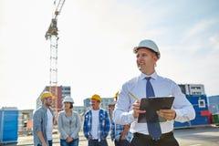 Constructeurs et architecte heureux au chantier de construction Image libre de droits