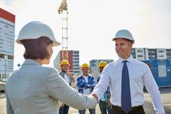 Constructeurs faisant la poignée de main sur le chantier de construction Image stock