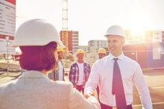 Constructeurs faisant la poignée de main sur le chantier de construction Photo stock