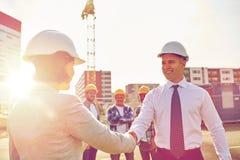 Constructeurs faisant la poignée de main sur le chantier de construction images stock