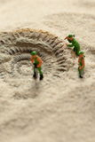 Constructeurs modèles miniatures indiquant le fossile d'ammonite en sable Image libre de droits
