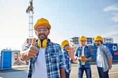 Constructeurs montrant des pouces au chantier de construction Image libre de droits