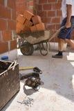 Constructeurs portant une brouette en construction Photos stock