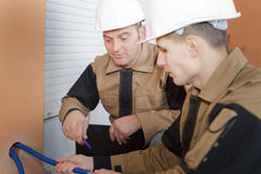 Constructeurs tenant l'isolation de tuyau sur des tuyaux d'eau chaude Photos libres de droits