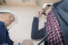 Constructeurs vérifiant le problème de fuite sur le toit photos stock