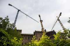 Constructing a building with big cranes. Cranes on a construction site royalty free stock photos