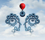 Constructing A Business Partnership. Concept with gears connected together shaped as a human head team with a red balloon placing a key cog in the center to Stock Photos