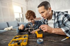 Serious boy holding a magnifying glass. Constructing. Good-looking concentrated loving dark-haired men showing instruments to his son while sitting at the table Stock Photography