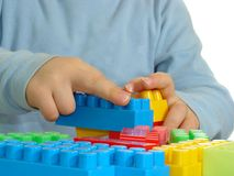 Constructing hands. Child hands constructing a toy brick structire Stock Photography