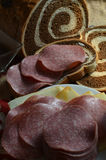 Constructing Salami and Cheese Sandwich on Marbled Rye bread in front of loaf royalty free stock photos