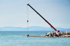 Constructing a wave breaker. A crane moving wave breaker stones with the stone just touching the sea Stock Photos