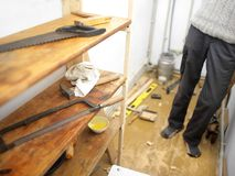 Constructing Wooden Shelves. Particular focus shot of a man standing in a messy room with unfinished wooden shelves Stock Photo