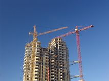 Construction 11. Construction works on a highrise building with cranes over a blue sky Royalty Free Stock Photography