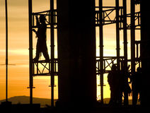 Construction. Silhouette of construction and workers at sunset royalty free stock photography