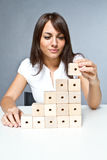 Construction. Young woman playing with wooden blocks Stock Photo