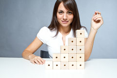 Construction. Young woman playing with wooden blocks stock photos
