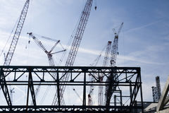 Construction 4. New industrial building construction site. Silhouettes of cranes and building frame against blue sky background Royalty Free Stock Photography