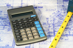 Construction. Blueprints with a calulator and tape measure Royalty Free Stock Photo