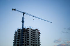 Construction. Crane near the building over the blue sky background Royalty Free Stock Photo