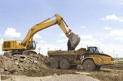 Construction. A hoe filling up a dump truck royalty free stock photos