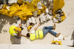 Construction accident. Construction worker has an accident while working on new house Royalty Free Stock Image