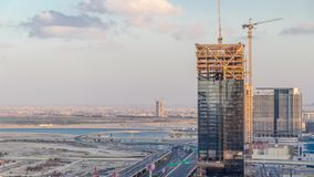 Construction activity in Dubai downtown with cranes and workers timelapse, UAE. Building of new skyscrapers and towers near crossroad junction stock footage