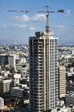 Construction in Tel-Aviv. Construction activity of a very tall skyscraper intended for use as an office building, on the background of the city of Tel-Aviv and Royalty Free Stock Photo