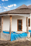 Construction of  adobe house with  thatched roof and plastic windows. Royalty Free Stock Photos