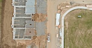 Construction of aerial top view on pouring the foundation for a new building with suburbs