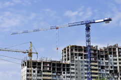 Construction of an apartment building. Two construction cranes and unfinished apartment house Stock Photography