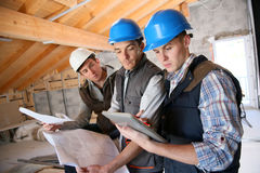 Construction apprentices working on plans Royalty Free Stock Photography