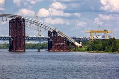 Construction of an arch bridge. Construction of an arch bridge across the river, erection of a metal structure from the shore through a reservoir Royalty Free Stock Photo