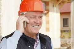 Construction architect making conversation. Portrait of senior construction architect while using his mobile Royalty Free Stock Photo