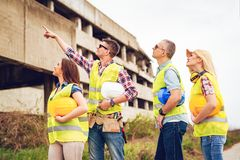 Let`s Start Over There!. Construction architects pointing at building damaged in the disaster Stock Photos