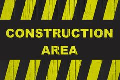 Construction area warning sign with yellow and black stripes painted over cracked wood. Stock Images