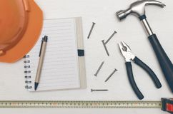 Construction background with copy space. Construction concept background with copy space. Blank note pad with empty paper sheet, pen and hammer with nails on Royalty Free Stock Images