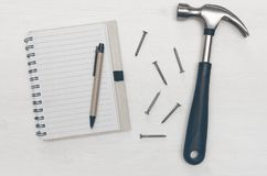 Construction background with copy space. Construction concept background with copy space. Blank note pad with empty paper sheet, pen and hammer with nails on Royalty Free Stock Photography