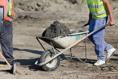 Construction barrow with concrete. Construction worker pushing barrow with concrete at building site royalty free stock photography