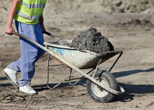 Construction barrow with concrete. Construction worker pushing barrow with concrete at building site stock photo