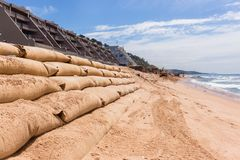 Construction Beach Ocean Erosion Repairs. Construction on beach water line coastline building repairs with sandbags buffer on sand dunes to protect road and Royalty Free Stock Photos