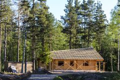 Construction of a beautiful house made of timber, harmoniously fitting into the nature of the North stock image