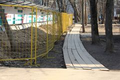 Construction is behind the fence. Around the construction paved the wooden road. Wooden road near the construction site. Nearby grow tall trees royalty free stock photography