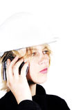 Construction blonde woman on the phone. A construction blonde women with safety helmet on the phone royalty free stock photo