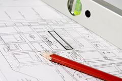 Construction blueprints. Spread out construction blueprints with a red pencil and a spirit level atop Stock Photo